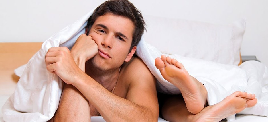 man's lying on a bed with the sole of his partner on his face