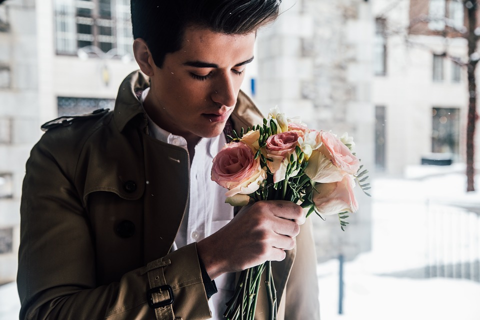 a man wearing white shirt and a brown coat holding roses